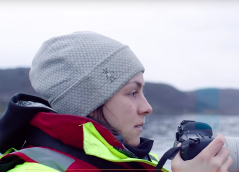 Lisa the arctic whale researcher with warm clothes and camera in hand.